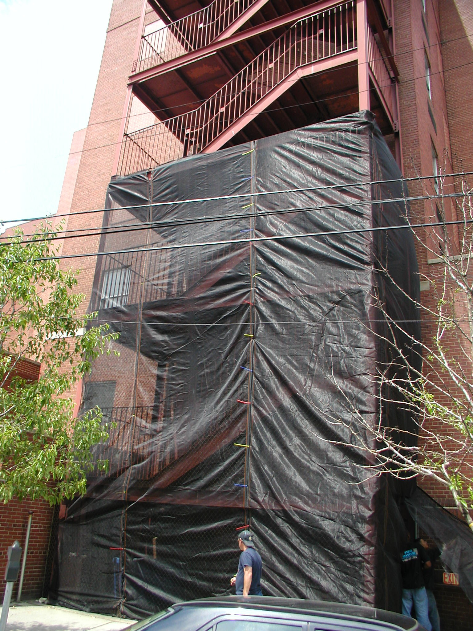 Structural commercial steel pan stair tower with structural framing, guardrail, stairs + landing, and protective debris mesh. (Manhattan, NY)